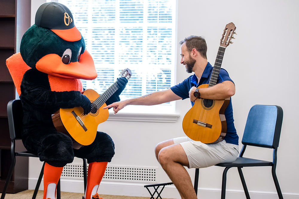 Baltimore School of Music owner and CEO James Lowe teaches the Oriole Bird how to play the guitar during a school open house.